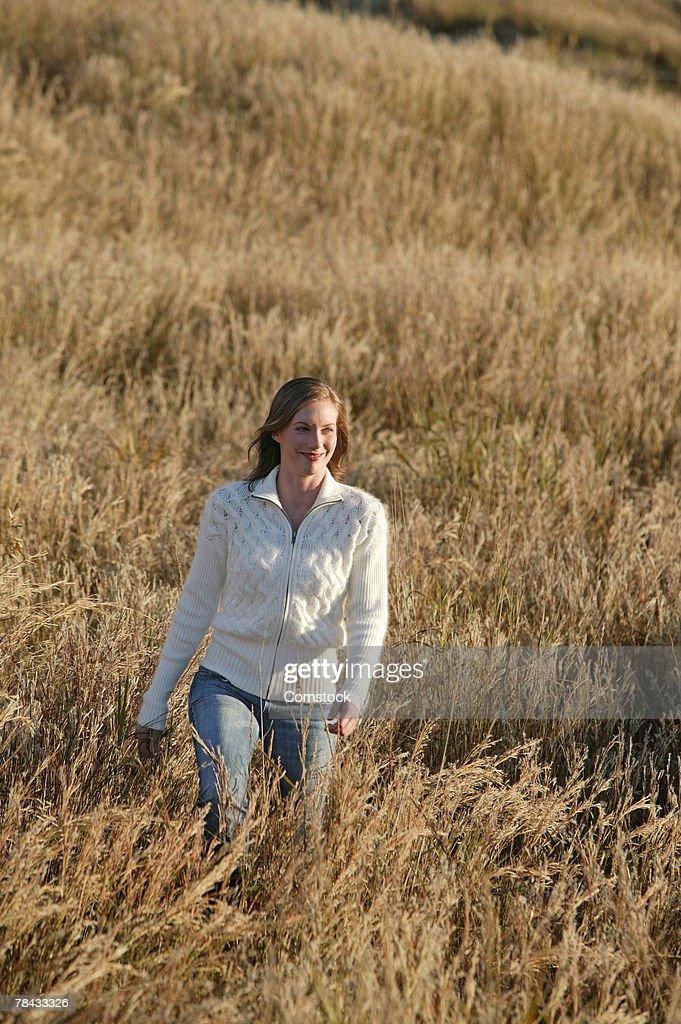 Smiling woman walking in a field : Stock Photo