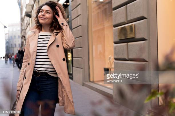 smiling woman walking in the city - coat stockfoto's en -beelden