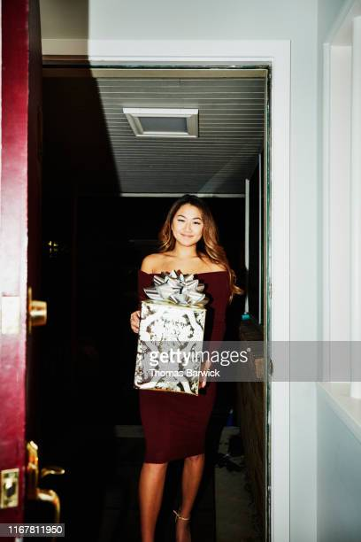 smiling woman walking into home with present for holiday party - maroon stock pictures, royalty-free photos & images