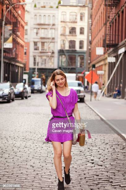 smiling woman walking on cobbled street in city - purple dress stock pictures, royalty-free photos & images