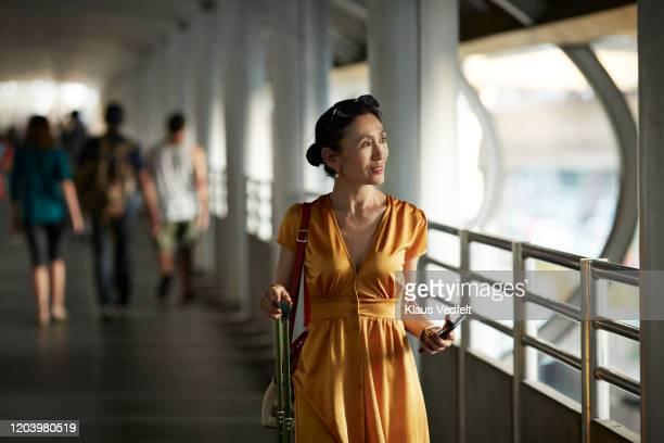 smiling woman walking on railroad station - une seule femme d'âge mûr photos et images de collection