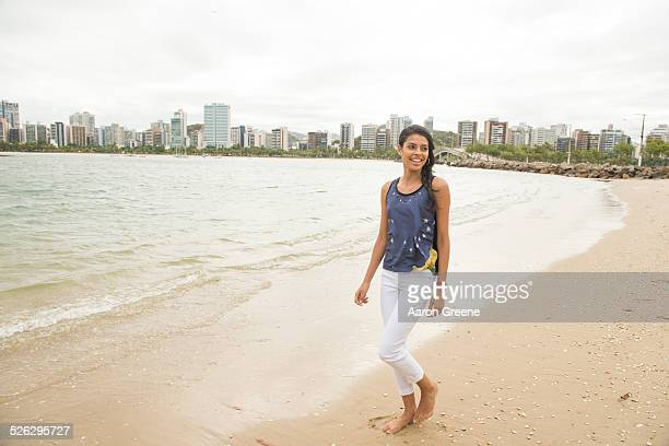 Smiling woman walking on urban beach