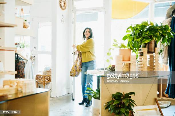 smiling woman walking through door into boutique - small business stock pictures, royalty-free photos & images