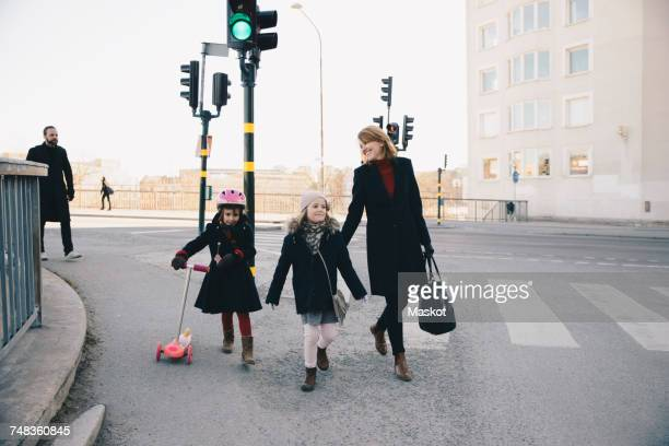 Smiling woman walking with daughters on city street against clear sky
