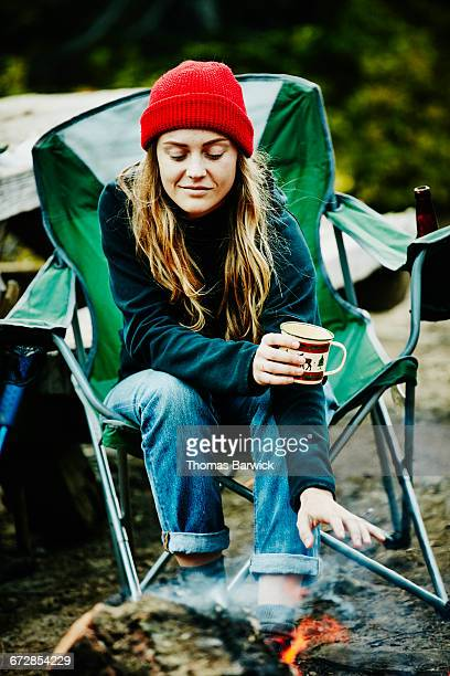 Smiling woman warming hands over campfire