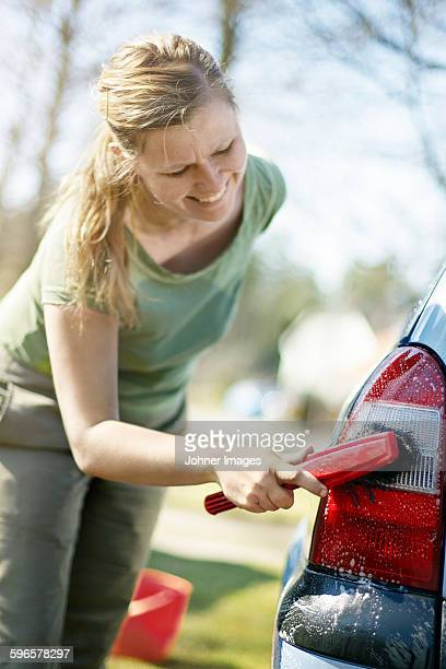 Smiling woman washing car