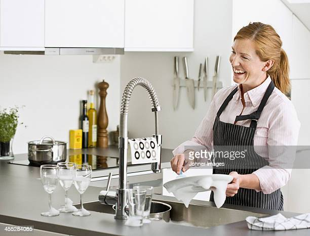 Smiling woman washing dishes