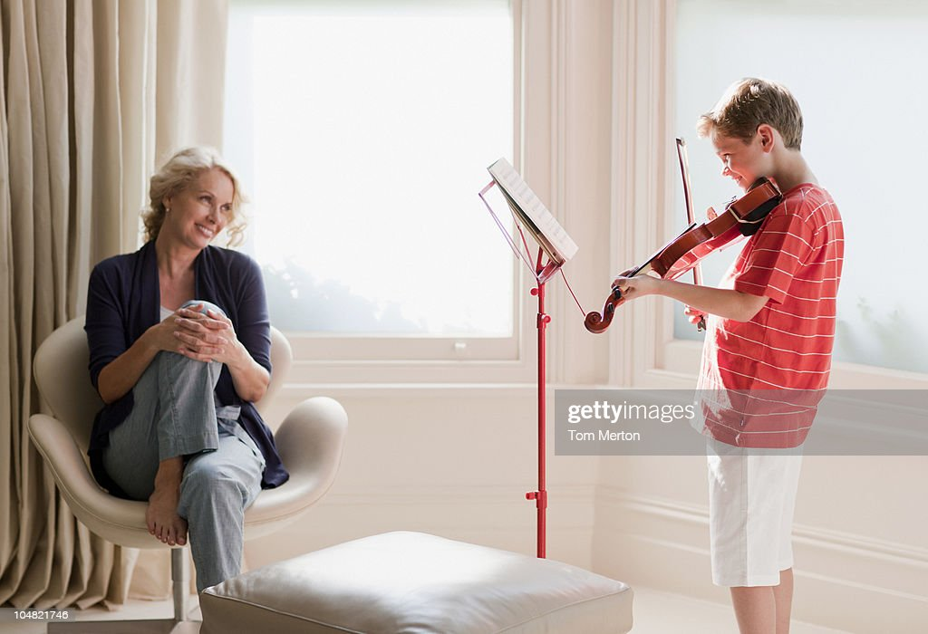 Smiling woman watching boy play violin : Stock Photo