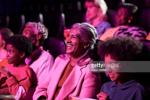 smiling woman watching movie with son in cinema hall - audience stock pictures, royalty-free photos & images