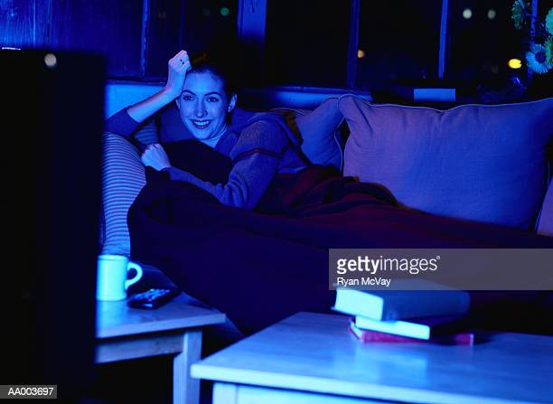 smiling woman watching television - night in fotografías e imágenes de stock