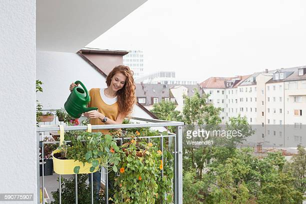 Smiling woman watering flowers on balcony