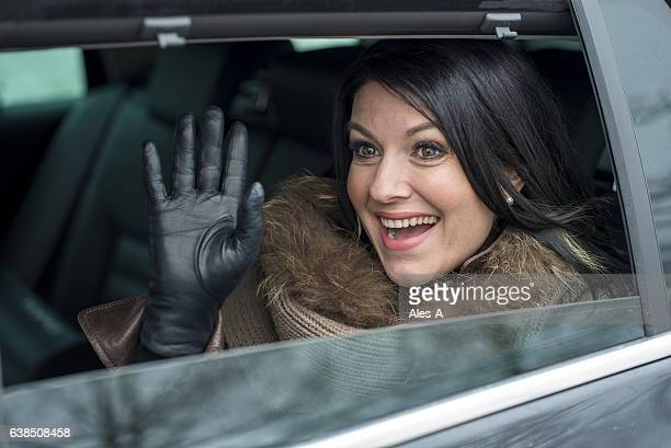 smiling woman waving through a car window - leather glove stock pictures, royalty-free photos & images