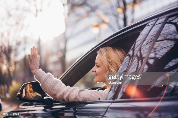 smiling woman waving through the window while driving a car. - waving stock pictures, royalty-free photos & images