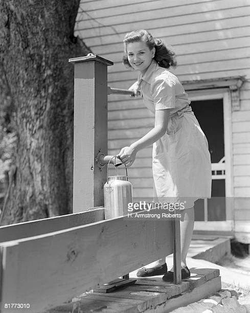 Smiling Woman Wearing A Plain Cotton Dress Filling A Container With Water At The Water Pump At The Back Of The White Wooden House Water Trough.