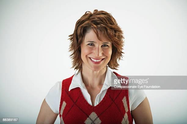 """smiling woman wearing argyle vest - """"compassionate eye"""" imagens e fotografias de stock"""