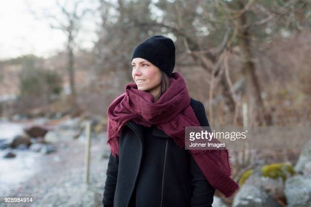 Smiling woman wearing big scarf in winter landscape