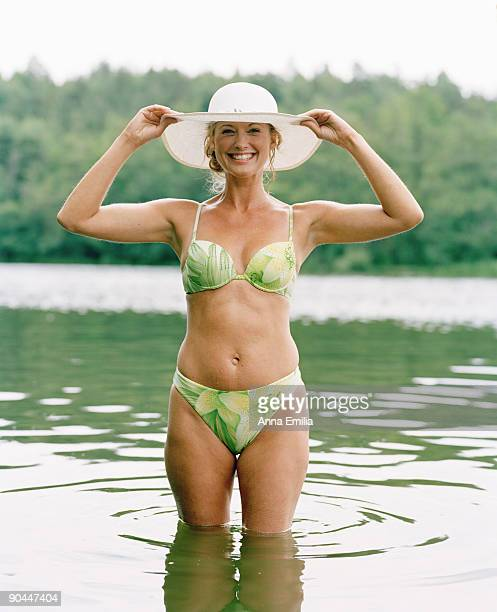 a smiling woman wearing bikini and a hat sweden. - one mature woman only stock pictures, royalty-free photos & images