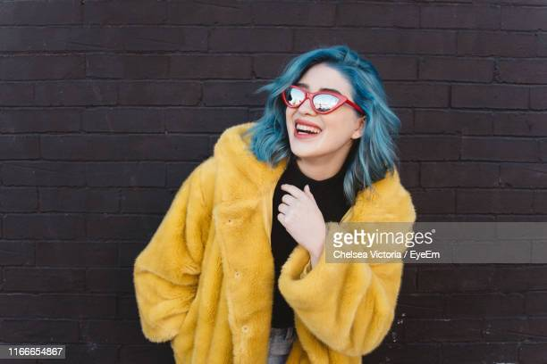 smiling woman wearing coat and sunglasses while standing against brick wall - hipster fotografías e imágenes de stock