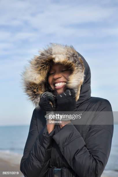 smiling woman wearing coat on beach - parka coat stock photos and pictures