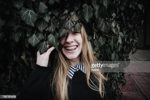 Smiling woman wearing dental braces hiding behind an ivy bush