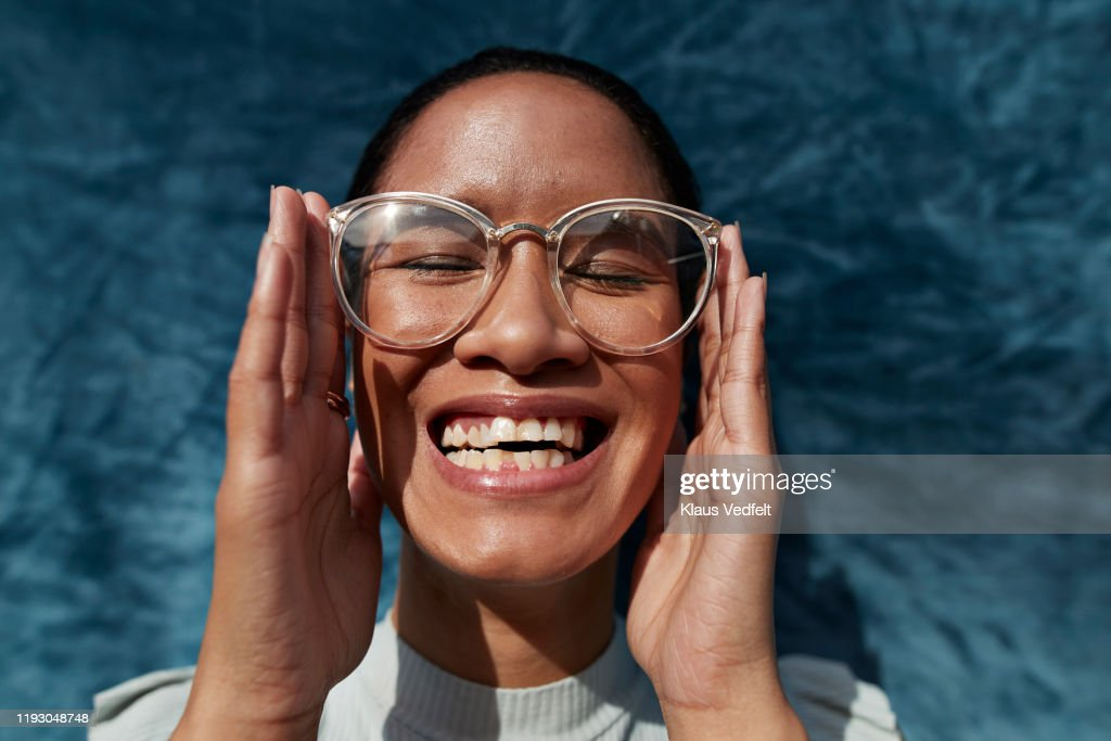 Smiling woman wearing eyeglasses against blue wall : Stock Photo