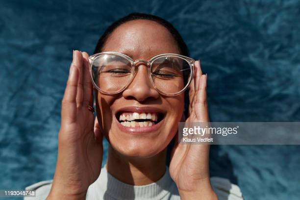 smiling woman wearing eyeglasses against blue wall - リアルライフ ストックフォトと画像