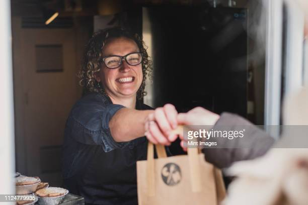 smiling woman wearing glasses handing  brown paper shopping bag through window of bakery. - local produce stock pictures, royalty-free photos & images