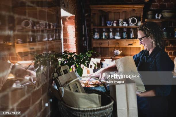 smiling woman wearing glasses placing freshly baked pies in brown paper shopping bag. - artisan stock photos and pictures