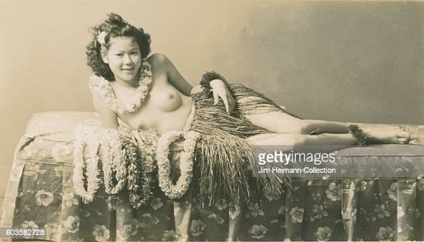 Smiling woman wearing grass skirt and lei reclines on bed Four leis are spread out in front of her