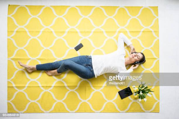 smiling woman wearing headphones lying on carpet with bunch of tulips - lying on back stock pictures, royalty-free photos & images