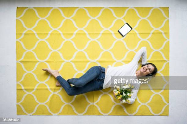 Smiling woman wearing headphones lying on carpet with bunch of tulips