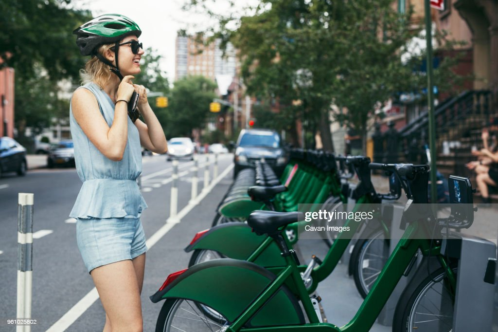 Smiling woman wearing helmet while standing by bicycles on street : Stock Photo