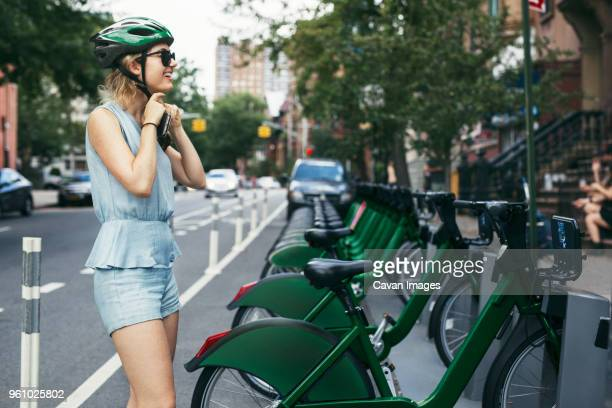 smiling woman wearing helmet while standing by bicycles on street - cavan images foto e immagini stock
