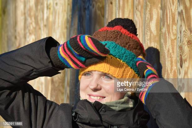 smiling woman wearing knit hat looking away - liga cerina stock pictures, royalty-free photos & images