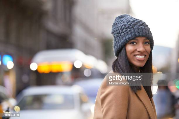 smiling woman wearing knit hat on city street - straight hair stock pictures, royalty-free photos & images