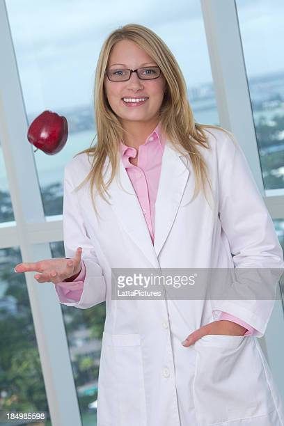 Smiling woman wearing lab coat and tossing apple mid air