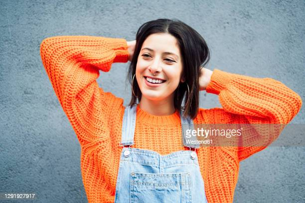 smiling woman wearing orange sweater looking away while standing against gray wall - オレンジ色のシャツ ストックフォトと画像