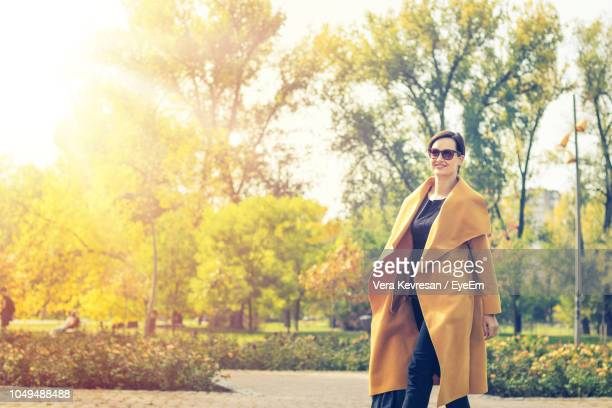 smiling woman wearing sunglasses and overcoat at park - overcoat stock pictures, royalty-free photos & images