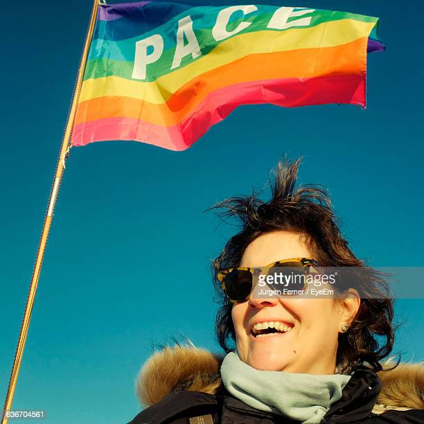 Smiling Woman Wearing Sunglasses Standing By Rainbow Flag Against Clear Sky