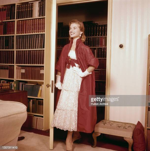 Smiling woman wears an ankle-length white lace dress, a long red coat with three-quarter sleeves and bow belt fastening, and white gloves, UK, circa...