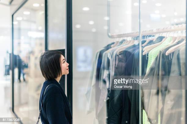 Smiling woman window shopping at storefront