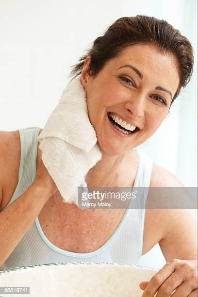 Smiling woman wiping her neck with a wash cloth.
