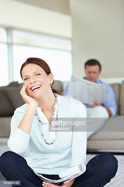 Lächelnde Frau mit einer Zeitschrift und Mann auf der Rückseite