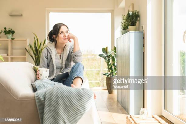 smiling woman with a mug and tablet sitting on the couch at home - natürlicher zustand stock-fotos und bilder