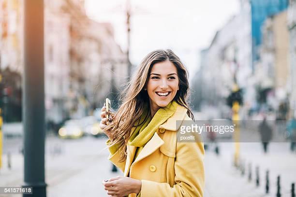 Mujer sonriente con teléfono en la calle