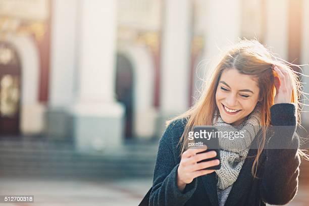 Femme souriante avec un téléphone