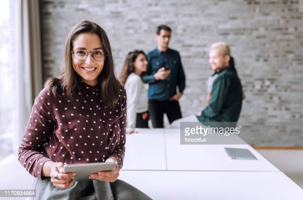 smiling woman with a table t in office - manager stock pictures, royalty-free photos & images