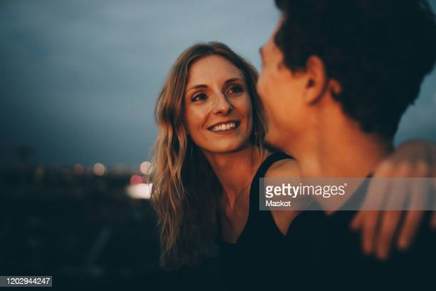 smiling woman with arm around looking at man while sitting on terrace at dusk - relationship stockfoto's en -beelden