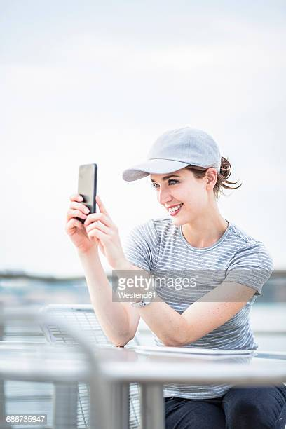 Smiling woman with basecap taking selfie with cell phone