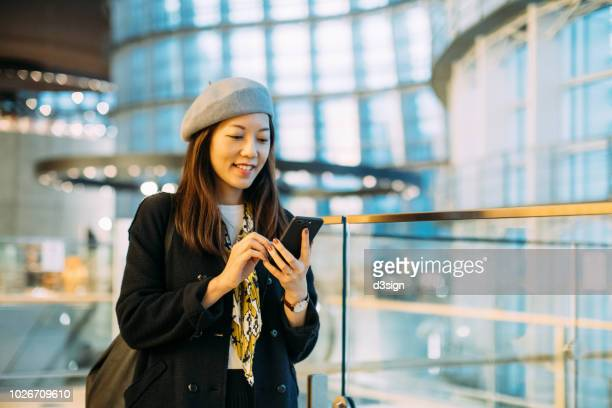 smiling woman with beret using smartphone by the glass fence on urban balcony - ベレー帽 ストックフォトと画像